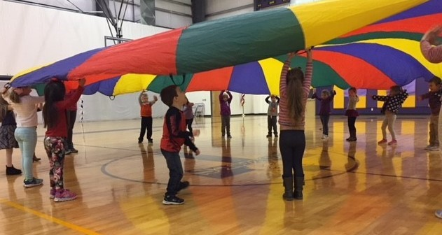 Preschool Students playing with a parachute